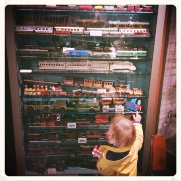 little-boy-looking-at-a-cabinet-of-toy-trains