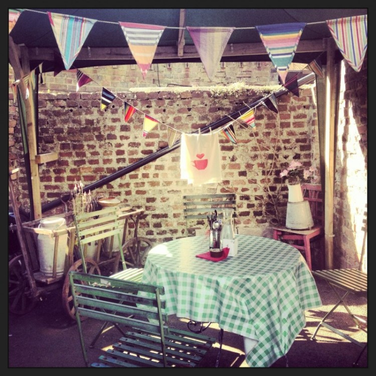 an-outside-cafe-table-with-bunting-above