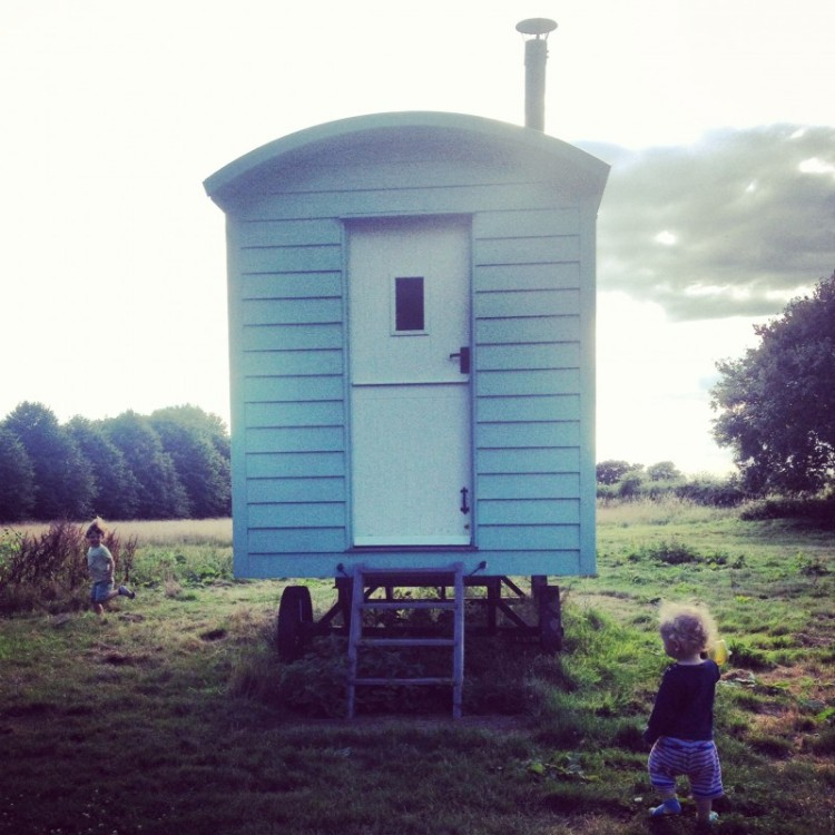 two-children-running-around-a-shepherds-hut