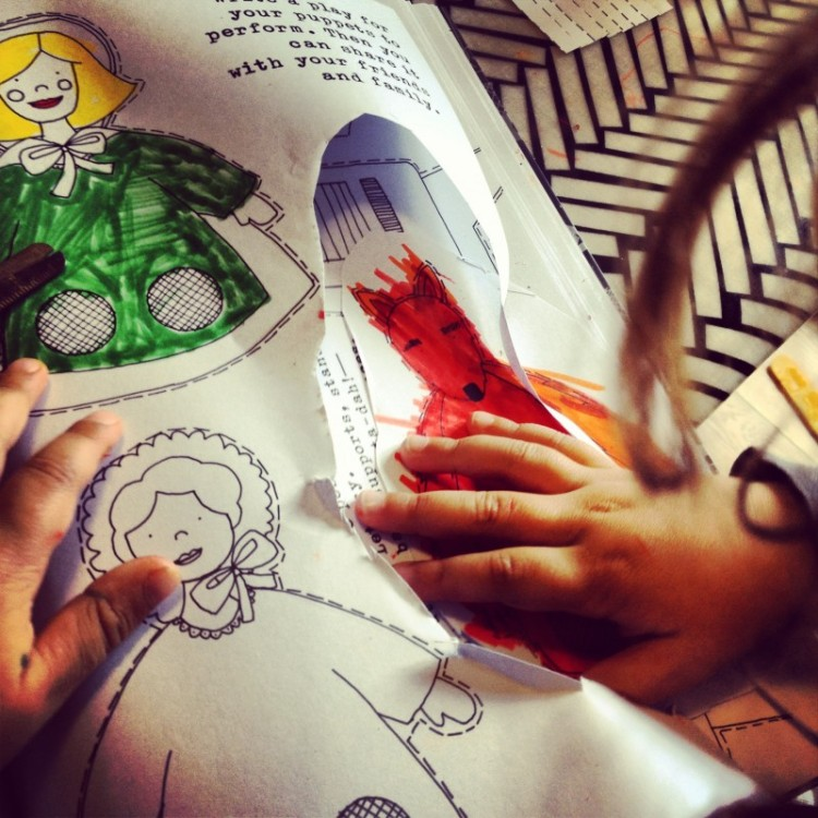 child-cutting-out-paper-puppets