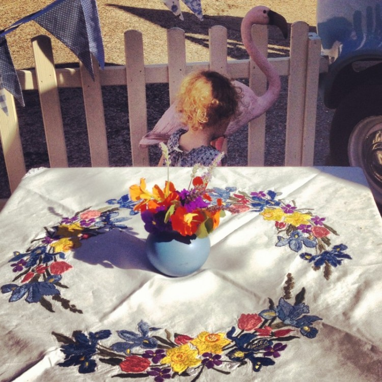 child-by-a-table-covered-in-flowers